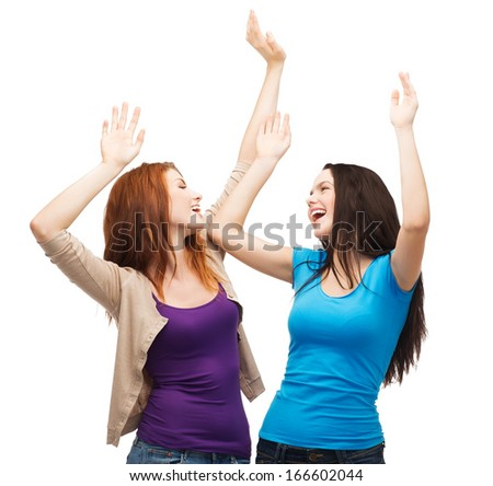 friendship, people and appiness concept - two happy dancing girls - stock photo