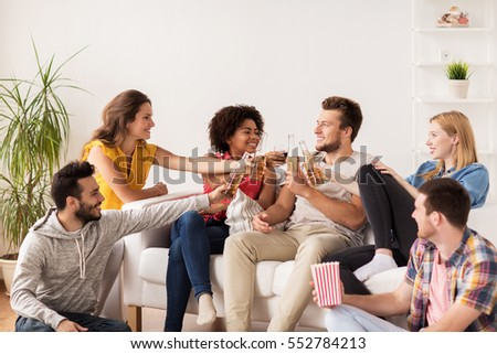 friendship, people and entertainment concept - happy friends with popcorn and beer talking at home