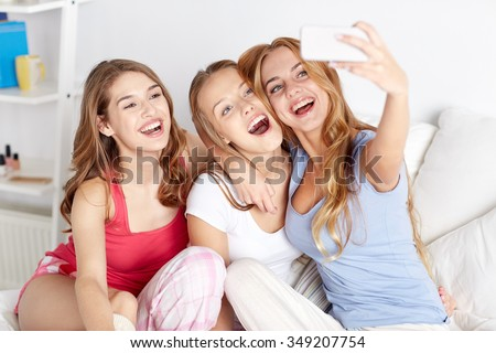 friendship, people, pajama party and technology concept - happy friends or teenage girls with smartphone taking selfie at home - stock photo