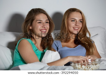 friendship, people, pajama party, entertainment and junk food concept - happy friends or teenage girls eating popcorn and watching movie or tv series at home - stock photo