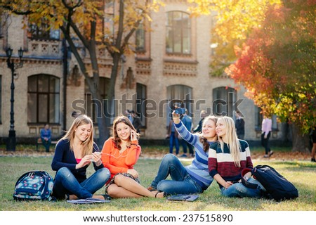Friendship, people, technology and education concept - group of smiling students with smart phones having fun together outdoors - stock photo