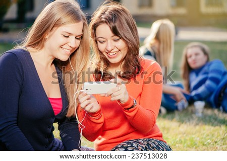 friendship, people, technology and education concept - two smiling young women with smart phone watching video together with two women talking in the background outdoors - stock photo