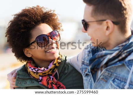 friendship, relations, tourism, travel and people concept - group of happy teenage friends or couple in sunglasses talking outdoors - stock photo