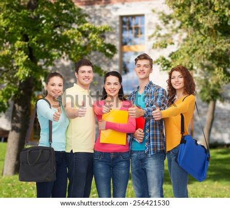 friendship, school, education, gesture and people concept - group of smiling teenagers with folders and school bags showing thumbs up over campus background - stock photo