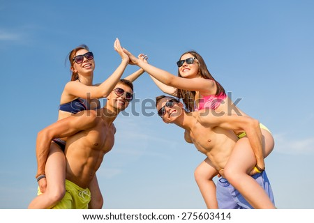 friendship, sea, gesture, holidays and people concept - group of smiling friends wearing swimwear having fun and making high five on beach - stock photo