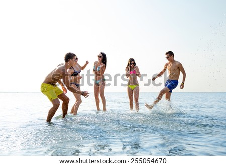 friendship, sea, summer vacation, holidays and people concept - group of happy friends having fun on beach - stock photo
