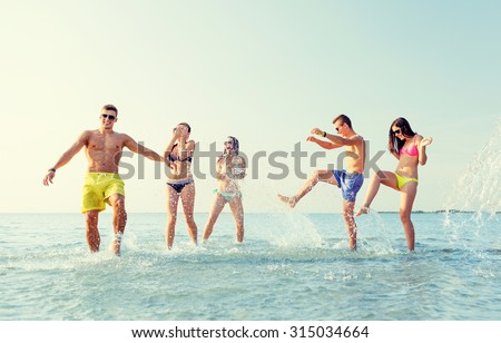 friendship, sea, summer vacation, holidays and people concept - group of happy friends having fun on beach