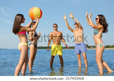 friendship, sea, summer vacation, holidays and people concept - group of smiling friends wearing swimwear and sunglasses talking on beach - stock photo