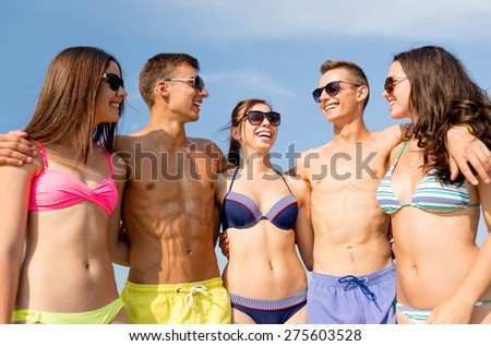 friendship, sea, summer vacation, holidays and people concept - group of smiling friends wearing swimwear and sunglasses talking and laughing on beach
