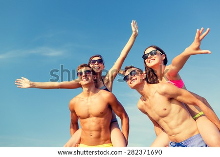 friendship, sea, summer vacation, holidays and people concept - group of smiling friends wearing swimwear and sunglasses having fun on beach - stock photo