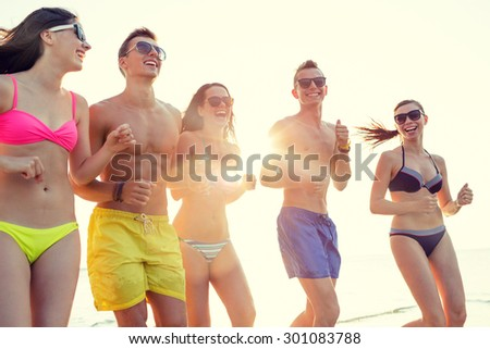 friendship, sea, summer vacation, holidays and people concept - group of smiling friends wearing swimwear and sunglasses running on beach - stock photo
