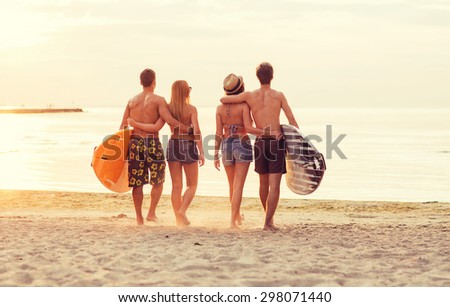 friendship, sea, summer vacation, water sport and people concept - group of smiling friends wearing swimwear with surfboards on beach from back - stock photo