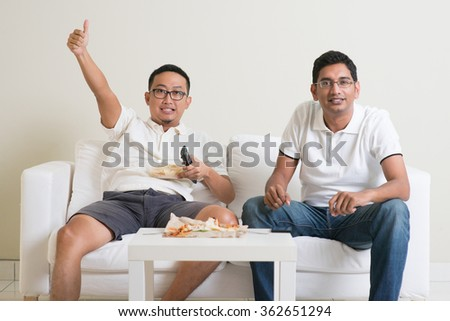 Friendship, sports and entertainment concept. Happy male friends watching sports together on tv at home. - stock photo