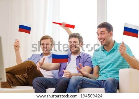 friendship, sports and entertainment concept - happy male friends with flags and vuvuzela supporting football team at home - stock photo
