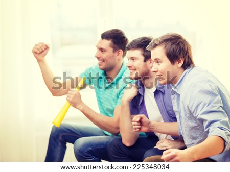 friendship, sports and entertainment - happy male friends with vuvuzela watching sports at home - stock photo