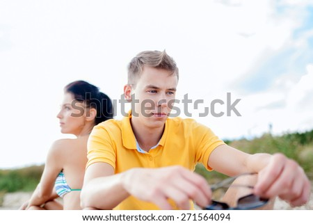 friendship, summer holidays, relations, break up and people concept - unhappy couple sitting on beach - stock photo