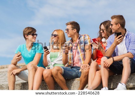 friendship, summer, technology and people concept - group of smiling friends with smartphones and headphones outdoors - stock photo