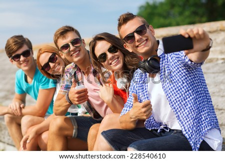 friendship, summer, technology, gesture and people concept - group of smiling friends with smartphone and headphones making selfie outdoors - stock photo