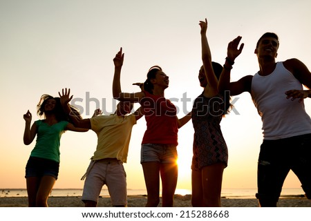 friendship, summer vacation, holidays, party and people concept - group of smiling friends dancing on beach - stock photo