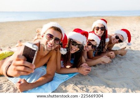 friendship, summer vacation, holidays, technology and people concept - group of friends in santa helper hats taking selfie with smartphone on beach - stock photo