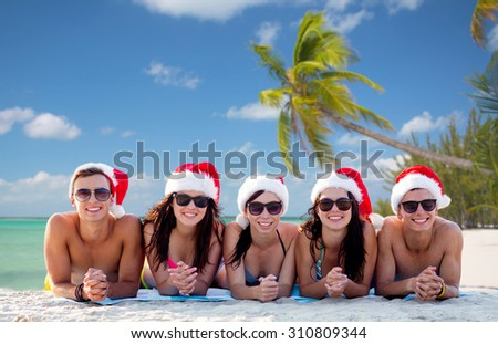 friendship, summer vacation, holidays, travel and people concept - group of friends in santa helper hats on beach