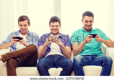 friendship, technology and home concept - smiling male friends with smartphones at home - stock photo