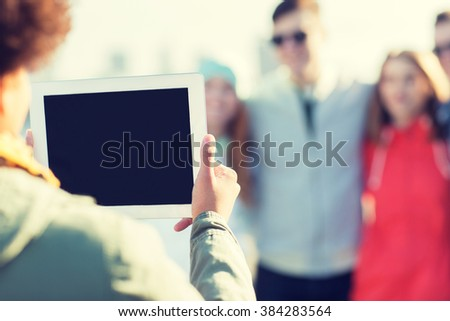 friendship, technology and people concept - close up of african woman with tablet pc computer photographing her happy friends outdoors - stock photo