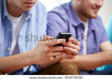 friendship, technology and people concept - close up of happy smiling male friends with smartphones texting at home - stock photo