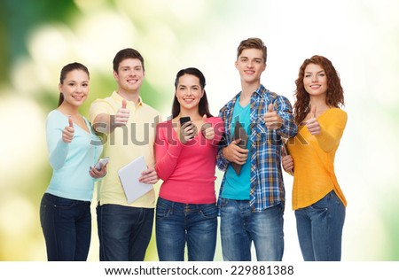 friendship, technology and people concept - group of smiling teenagers with smartphones and tablet pc computers showing thumbs up over green background