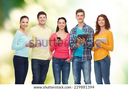 friendship, technology and people concept - group of smiling teenagers with smartphones and tablet pc computers over green background - stock photo