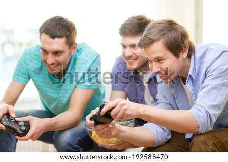 friendship, technology, games and home concept - smiling male friends playing video games at home - stock photo