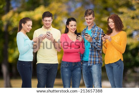 friendship, technology, nature and people concept - group of smiling teenagers with smartphones over park background