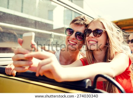 friendship, tourism, summer vacation, technology and people concept - smiling couple with smartphone traveling by tour bus and making selfie - stock photo
