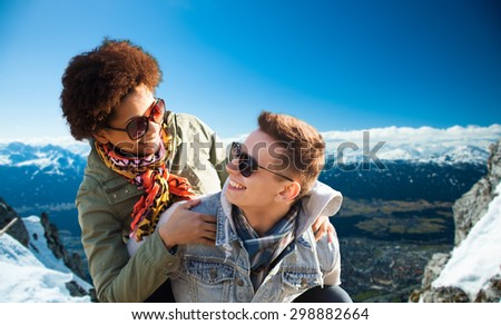 friendship, travel, tourism and people concept - happy international teenage couple in shades having fun over alps mountains in austria background - stock photo