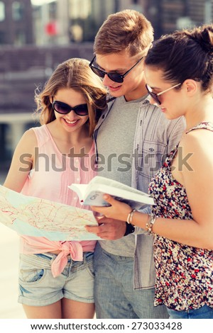 friendship, travel, tourism, vacation and people concept - smiling friends with map and city guide outdoors - stock photo