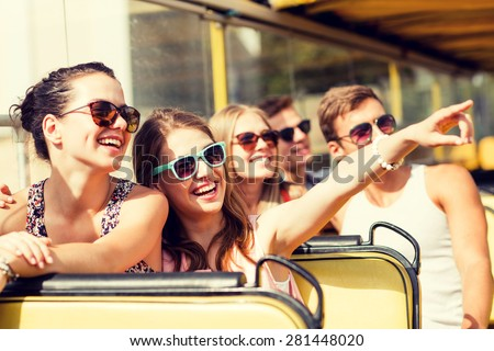 friendship, travel, vacation, summer and people concept - group of smiling friends traveling by tour bus - stock photo