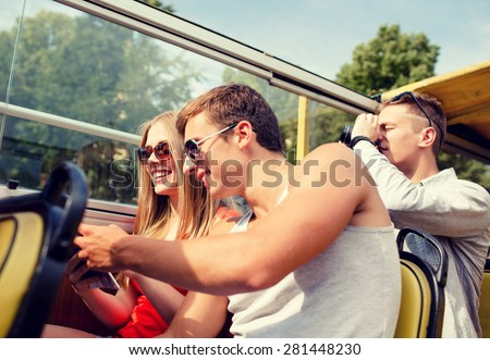 friendship, travel, vacation, summer and people concept - smiling couple looking to city guide book traveling by tour bus - stock photo
