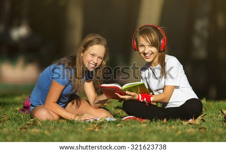 Friendship.Two adorable cute caucasian girls, lying in the park in a fine sunny afternoon, with  books, educating themselves and having fun - stock photo