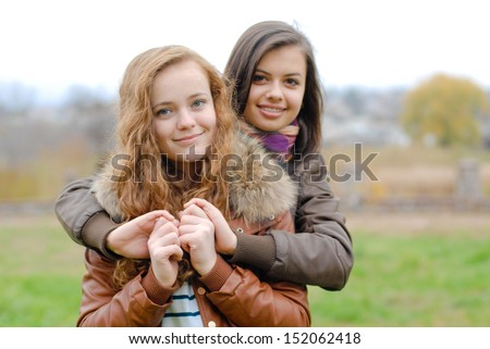 Friendship - Two best girlfriends hugging each other having fun outdoors happy smiling - stock photo