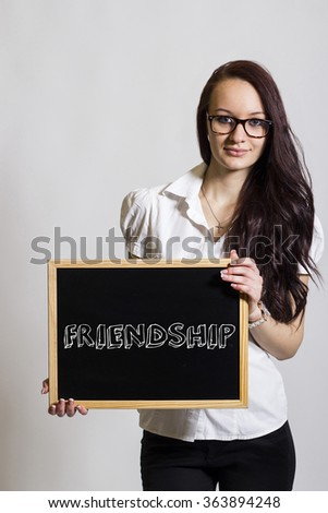 FRIENDSHIP - Young businesswoman holding chalkboard - vertical image