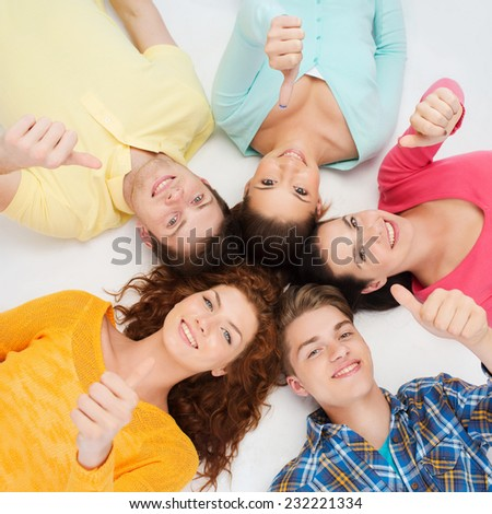 friendship, youth, gesture and people - group of smiling teenagers lying on floor in a circle and showing thumbs up - stock photo