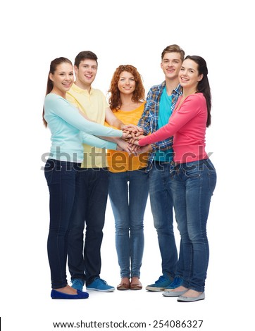 friendship, youth, gesture and people - group of smiling teenagers with hands on top of each other
