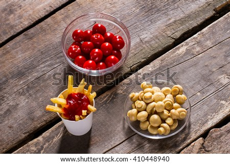Fries with tomatoes and mushrooms. Champignons and tomatoes with fries. Wooden table with tasty food. Delicious high-calorie snack. - stock photo