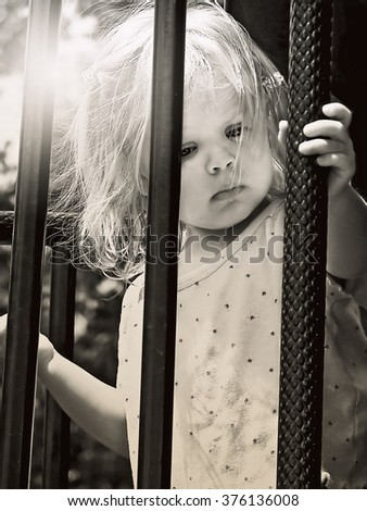 frighted little girl gripping cage bars with sun flare lighting - stock photo