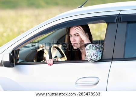 frightened  angry woman looking out  window of car