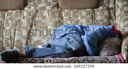 Frightened boy in jeans curled up on bed - stock photo