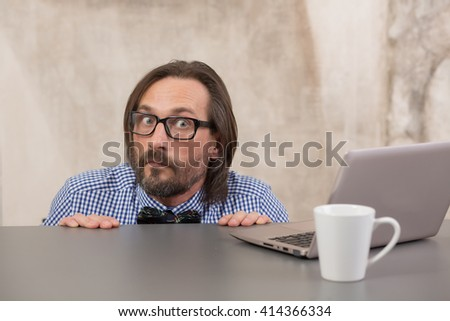 Frightened businessman hiding under table from taxmen. Handsome man in glasses looking at camera. - stock photo