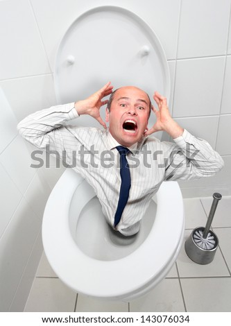 Frightened businessman screaming from toilet bowl. Economic crisis or bankruptcy metaphor. - stock photo