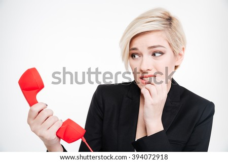 Frightened businesswoman holding retro phone tube isolated on a white background - stock photo