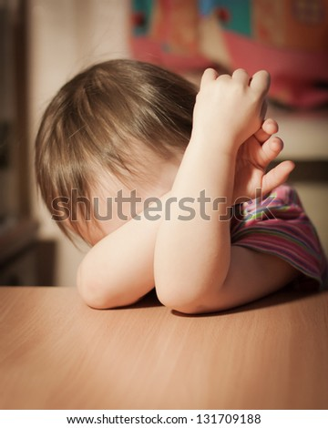 Frightened child closed his hands over eyes. - stock photo